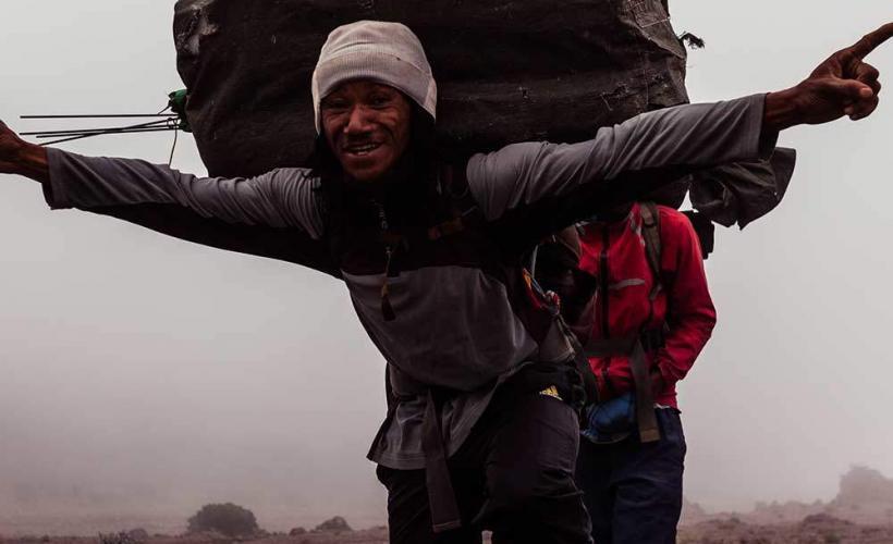 Glad bärare på väg mot Kilimanjaro